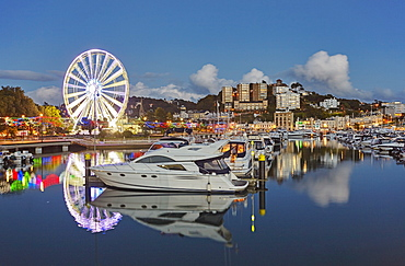 An atmospheric dusk view across Torquay Marina to the town of Torquay, on the south coast of Devon, England, United Kingdom, Europe