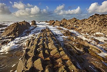 Surf rolling onto a rocky Atlantic shore, at Widemouth Bay, near Bude, Cornwall, southwest England, United Kingdom, Europe