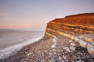 Evening light on rocks and the cliff at Kilve beach, Kilve, near Nether Stowey, Somerset, England, United Kingdom, Europe