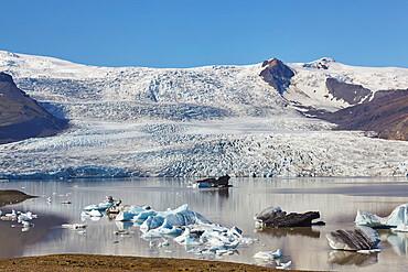 A glacier pouring down off the Vatnajokull icecap: the Fjallsjokull Glacier and Fjallsarlon lagoon, near Jokulsarlon, Iceland.