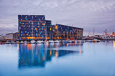 An evening view of the modern Harpa concert hall, beside the old harbour in Reykjavik, southwest Iceland.