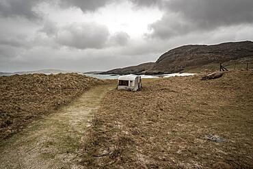Abandoned caravan at Cleit Beach, Barra, Outer Hebrids. Storm. Rain.