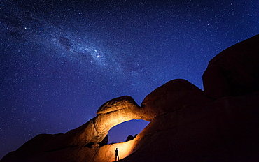 Tourist under the Rock Arch bridge in the Spitzkoppe region with a view of the Milky Way, Erongo region, Namibia, Africa