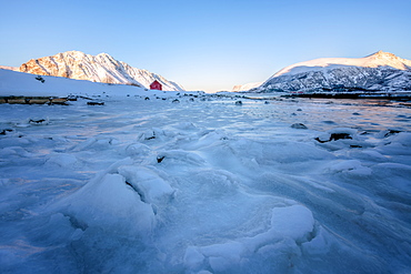 Rorbuer (fisherman's hut) on a frozen lake, Lofoten, Nordland, Arctic, Norway, Europe