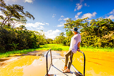 Woman searching for wildlife on a boat tour of the Amazon River, Peru, South America