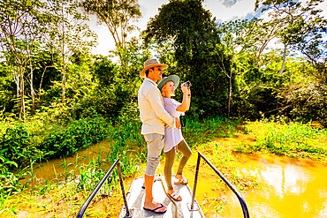 Couple searching for wildlife on a boat tour of the Amazon River, Peru, South America