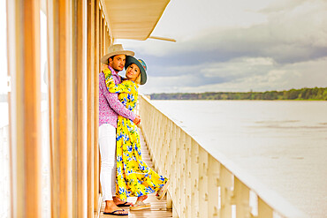Couple posing for the camera overlooking the Amazon River aboard a river boat, Peru, South America