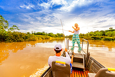 Woman and man fishing on small boat in the Amazon River, Peru, South America