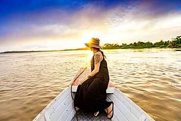 Woman enjoying sunset on the river, Amazon River, Peru, South America