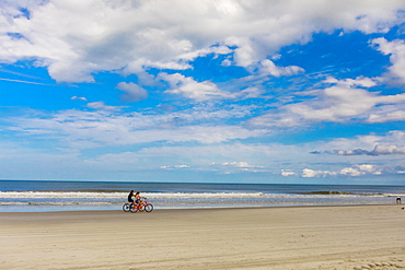 Couple bike riding on Jacksonville beach after it reopened during the Covid-19 Pandemic, Florida, United States of America, North America