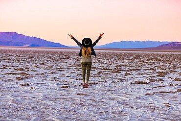 Model posing for the camera at sunset over the salt flats of the Mesquite Dunes, California, United States of America, North America