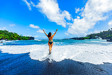 Woman enjoying the sun on one of Maui's black sand beaches, Maui, Hawaii, United States of America, North America