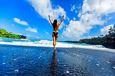 Woman enjoying the sun on one of Maui's black sand beaches, Hawaii, United States of America, North America
