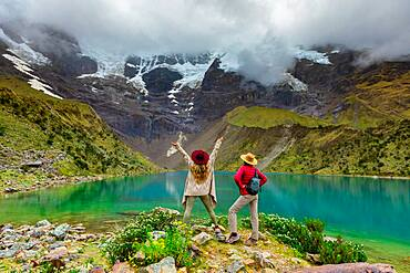 Two woman enjoying the view of crystal clear Humantay Lake, Cusco, Peru, South America