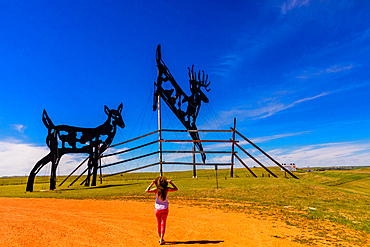 Woman in The Enchanted Highway, a collection of large scrap metal sculptures constructed at intervals along a two-lane highway.