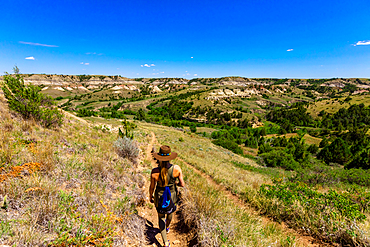Woman hiking along The Petrified Forest Loop Trail insideTheodore Roosevelt National Park.