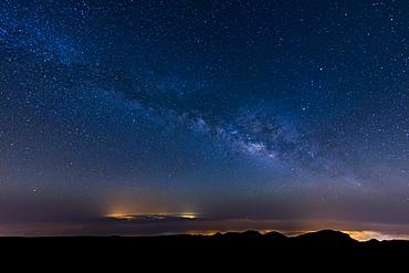 The Milky Way arcs above the city lights of Las Palmas De Gran Canaria, Canary Islands, Spain, Europe