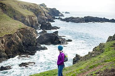 A woman hiking the coastal path on the west side of The Lizard Peninsula, Cornwall, England, United Kingdom, Europe