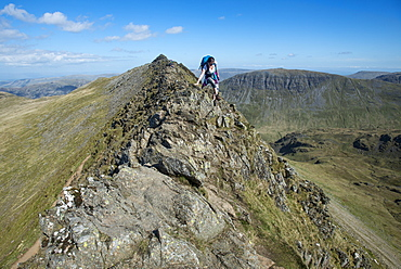 A woman on top of Striding Edge facing towards Ullswater in the English Lake District, Lake District National Park, Cumbria, England, United Kingdom, Europe