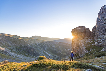 The last rays of sun disappear behind a rock face after a day of trekking in the Rila Mountains, Bulgaria, Europe