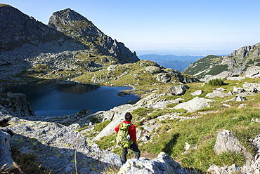 Hiking next to the clear water of Elenino Lake near Maliovitsa in the Rila Mountains, Bulgaria, Europe