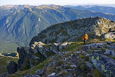 A hiker climbs along a high ridge near Maliovitsa in the Rila Mountains with distant views of valleys and hills, Bulgaria, Europe