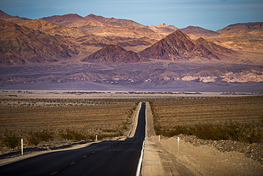 Highway through Death Valley with mountains in the distance, California, United States of America, North America