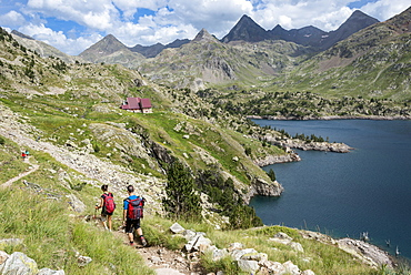 Hikers make their way along the the long distance footpath called the GR11 towards Refugio Respomuso in the Spanish Pyrenees, Huesca, Spain, Europe