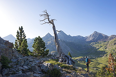A walker takes in a view of the Pyrenees from near Refugio Respomuso along the GR11 long distance trekking path, Huesca, Spain, Europe