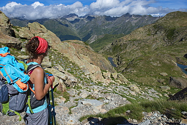 A hiker looks out at the Pyrenees mountains from the top of Col Peyreget while hiking the GR10 trekking trail, Pyrenees Atlantiques, France, Europe