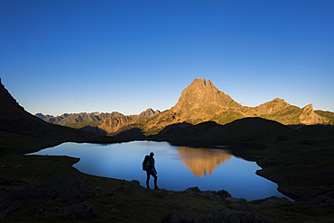 Taking in the view of Midi d'Ossau beyond Lac Gentau beside the GR10 trekking route in the French Pyrenees, Pyrenees Atlantiques, France, Europe