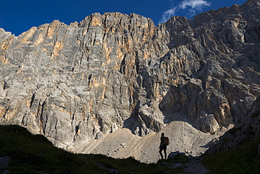 A trekker takes a break from the trail under the impressive northwest vertical wall of Monte Civetta in the Dolomites, Belluno, Veneto, Italy, Europe