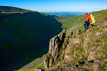 A man hiking the Pennine Way sits on the edge of the huge escarpment in the Yorkshire Dales called Highcup Nick