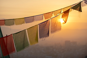 Prayer flags at Swayambhunath (Monkey Temple) in front of the city at sunrise, Kathmandu Valley, Nepal, Asia