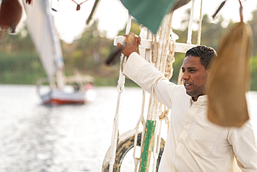 An Egyptian man holiding the mast while sailng a traditional Felucca sailboat with wooden masts and cotton sails on the Nile, Aswan, Egypt, North Africa, Africa