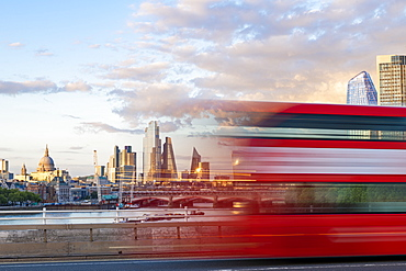 A red London bus goes past in a blur across Waterloo Bridge with the City of London and Southbank in distance, London, England, United Kingdom, Europe