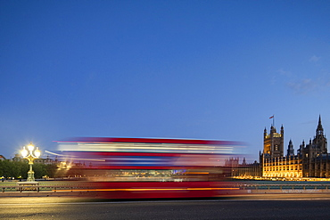 A red London bus goes past in a blur across Westminster Bridge, London, England, United Kingdom, Europe