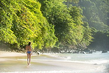 A woman walking on the beach at Castara Bay on the Caribbean island of Tobago, Trinidad and Tobago, West Indies, Caribbean, Central America