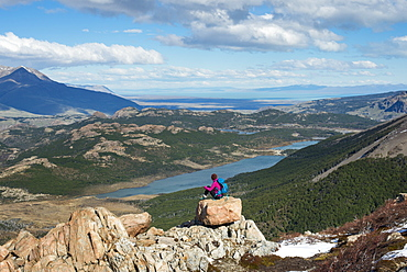 A woman takes a break from hiking the trail in El Chalten National Park to take in the view, Lake Vied, Patagonia, Argentina, South America