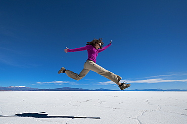 A girl leaps into the air at the Salinas Grandes (salt flats) near Purmamarca, Argentina, South America