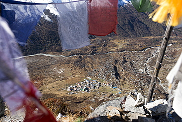 A view of Kyanjin Gompa in the Langtang valley, seen through Buddhist prayer flags on the top of Kyanjin Ri, Langtang, Nepal, Himalayas, Asia