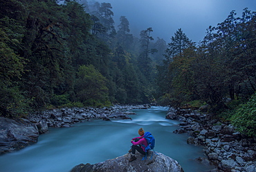A woman takes a break from the trail and sits beside the Langtang Khola near the little village of Riverside on a misty evening, Nepal, Himalayas, Asia