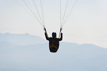 A paraglider flies above Pokhara, Nepal, Himalayas, Asia