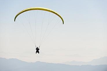 Paraglider flies above Pokhara, Nepal, Himalayas, Asia