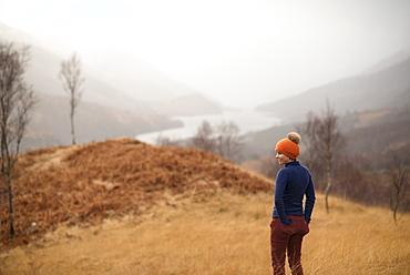 A woman walking near Kinlochlevan with a misty view towards Loch Leven, Perth and Kinross, Highlands, Scotland, United Kingdom, Europe