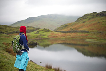 A woman looks out over Alcock Tarn near Grasmere, Lake District, Cumbria, England, United Kingdom, Europe
