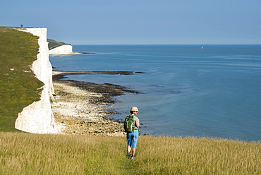 A woman walks along the cliffs near Beachy Head with views of the Seven Sisters coastline in the distance, South Downs National Park, East Sussex, England, United Kingdom, Europe