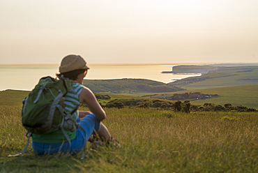 A woman looks out to sea near Beachy Head with views of the Seven Sisters coastline in the distance, South Downs National Park, East Sussex, England, United Kingdom, Europe
