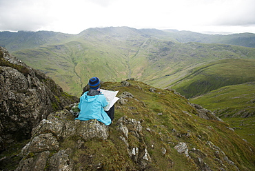 A woman stops near Stickle Pike in The Lake District to check her bearings on a map, Cumbria, England, United Kingdom, Europe