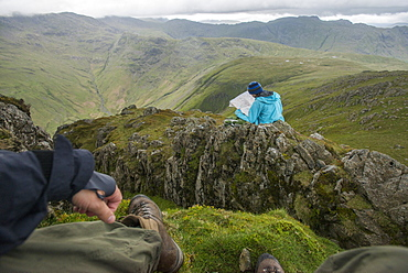 A woman checks her map while looking towards Great Langdale valley from the Langdale Pikes, Lake District National Park, Cumbria, England, United Kingdom, Europe